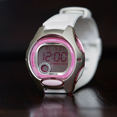 CASIO<sup>&reg;</sup> Women's Digital Watch - This digital women's watch has a white band with silver case and pretty pink dial. Features include an alarm, stopwatch, dual time, LED light and date display. Water resistant to 50 meters.
